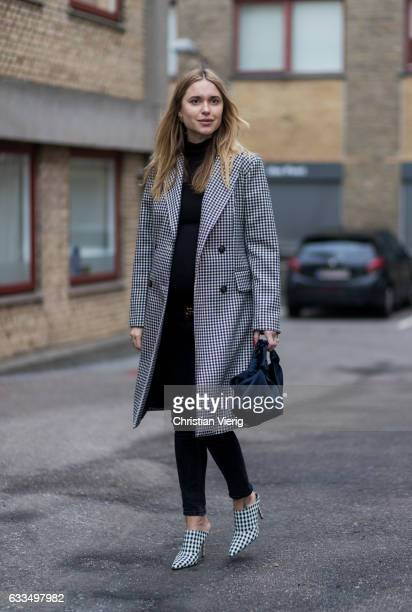Pernille Teisbaek wearing a checked coat Gucci belt checked heels black denim jeans outside Baum Pferdgarten at the Copenhagen Fashion Week...