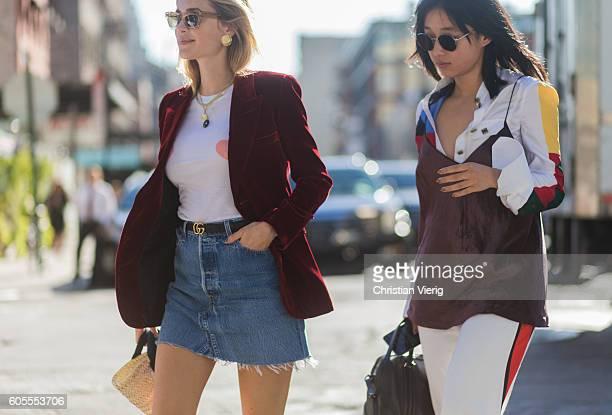 Pernille Teisbaek wearing a velvet blazer Gucci belt denim mini skirt and Margaret Zhang outside Tory Burch on September 13 2016 in New York City