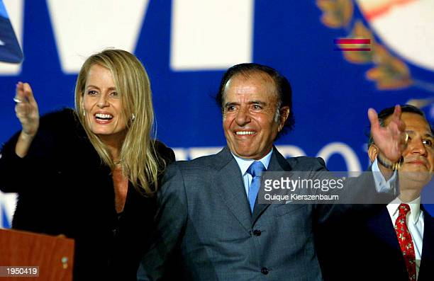 Peronist party presidential candidate Carlos Menem along with his wife Cecilia Bolocco salutes his supporters during a campaign rally April 24 2003...