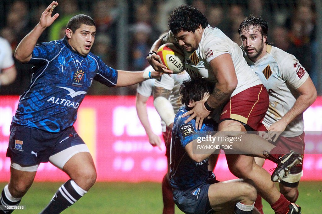 Perpignan's prop Romain Tao (R) is tackled by Montpellier's prop Juan Figallo during the French Top 14 rugby Union match between Perpignan and Montpellier, on December 22, 2012, in Perpignan. ROIG