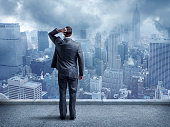Perplexed Businessman Looking At Cityscape