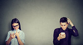 Perplexed young man and woman looking at mobile phone