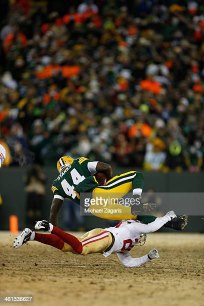 Perrish Cox of the San Francisco 49ers upends James Starks of the Green Bay Packers during the game against the Green Bay Packers at Lambeau Field on...