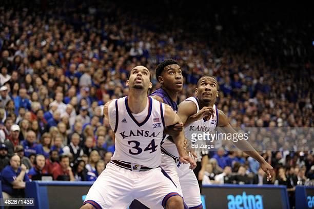 Perry Ellis of and Wayne Selden Jr #1 of the Kansas Jayhawks block out Wesley Iwundu of the Kansas State Wildcats on a free throw at Allen Field...
