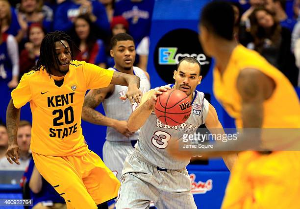 Perry Ellis of the Kansas Jayhawks battles Marquiez Lawrence of the Kent State Golden Flashes for the ball during the game at Allen Fieldhouse on...