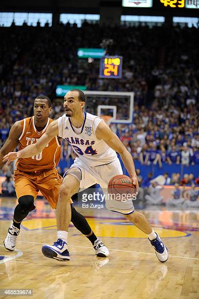 Perry Ellis of the Kansas Jayhawks drives to the goal against Jonathan Holmes of the Texas Longhorns at Allen Fieldhouse on February 28 2015 in...