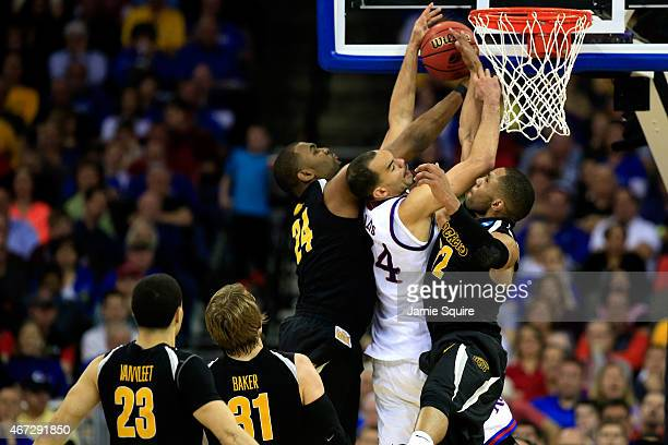 Perry Ellis of the Kansas Jayhawks has a shot blocked by Shaquille Morris and teammate Tekele Cotton of the Wichita State Shockers in the second half...