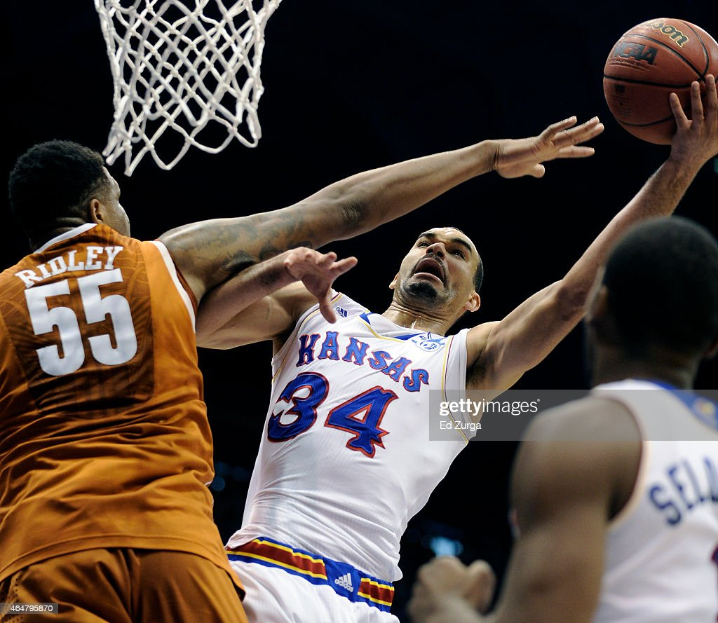 Perry Ellis of the Kansas Jayhawks shoots against Cameron Ridley of the Texas Longhorns in the first half at Allen Fieldhouse on February 28 2015 in...
