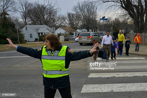 Perry Tsianaks a crossing guard directs traffic as Animesh Gupta wearing light collared shirt takes his two children ages 5 and 7 to school on...