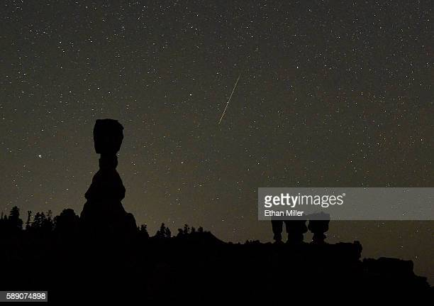 Perseid meteor streaks across the sky between the hoodoos named Thor's Hammer and the Three Sisters early on August 13 2016 in Bryce Canyon National...