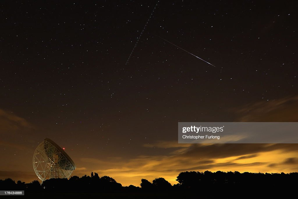 Perseid meteor streaks across the sky over the Lovell Radio Telescope at Jodrell Bank on August 13, 2013 in Holmes Chapel, United Kingdom.The annual display, known as the Perseid shower because the meteors appear to radiate from the constellation Perseus in the northeastern sky, is a result of Earth's orbit passing through debris from the comet Swift-Tuttle.
