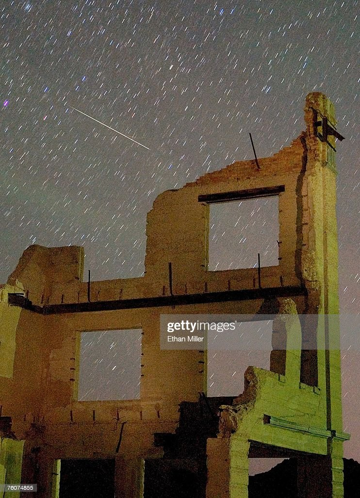 A Perseid meteor streaks across the sky over the ruins of the Cook Bank building early August 13, 2007 in the ghost town of Rhyolite, Nevada. The meteor display, known as the Perseid shower because it appears to radiate from the constellation Perseus in the northeastern sky, is a result of Earth's orbit passing through debris from the comet Swift-Tuttle. This weekend was considered the peak of the shower, which is visible every August.