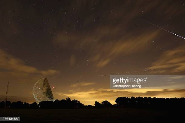 Perseid meteor streaks across the sky past the light trail of an aircraft over the Lovell Radio Telescope at Jodrell Bank on August 13 2013 in Holmes...