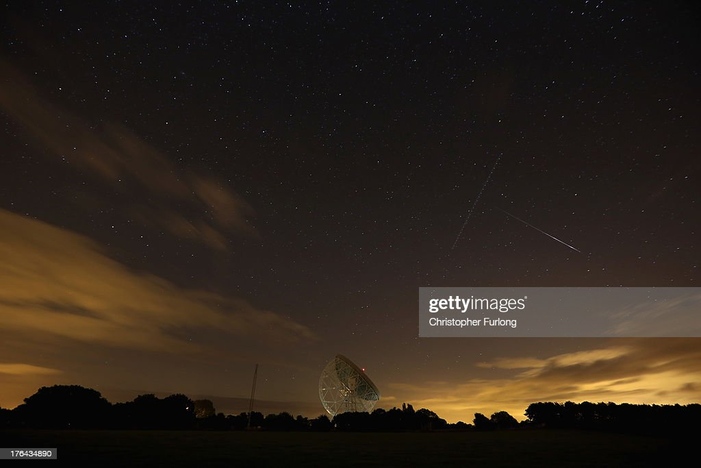 Perseid meteor (R) streaks across the sky past the light trail of an aircraft over the Lovell Radio Telescope at Jodrell Bank on August 13, 2013 in Holmes Chapel, United Kingdom.The annual display, known as the Perseid shower because the meteors appear to radiate from the constellation Perseus in the northeastern sky, is a result of Earth's orbit passing through debris from the comet Swift-Tuttle.