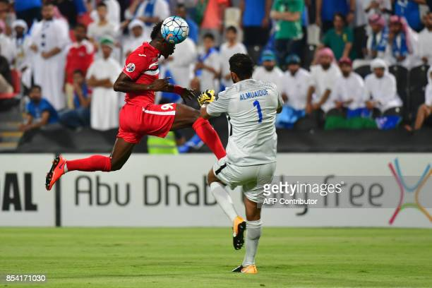 Persepolis' forward Godwin Mensha heads the ball as he is met by Al Hilal's goalkeeper Abdullah Almuaiouf during the first leg of their AFC Champions...