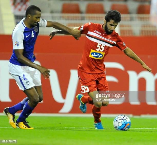 Persepolis' midfielder Bashar Resan dribbles past AlHilal's defender Abdulla Aldossary during the Asian Champions League semifinal football match...
