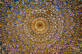 Abstract pattern inside a ceiling dome using the Persian and Islamic architectural style and decoration.