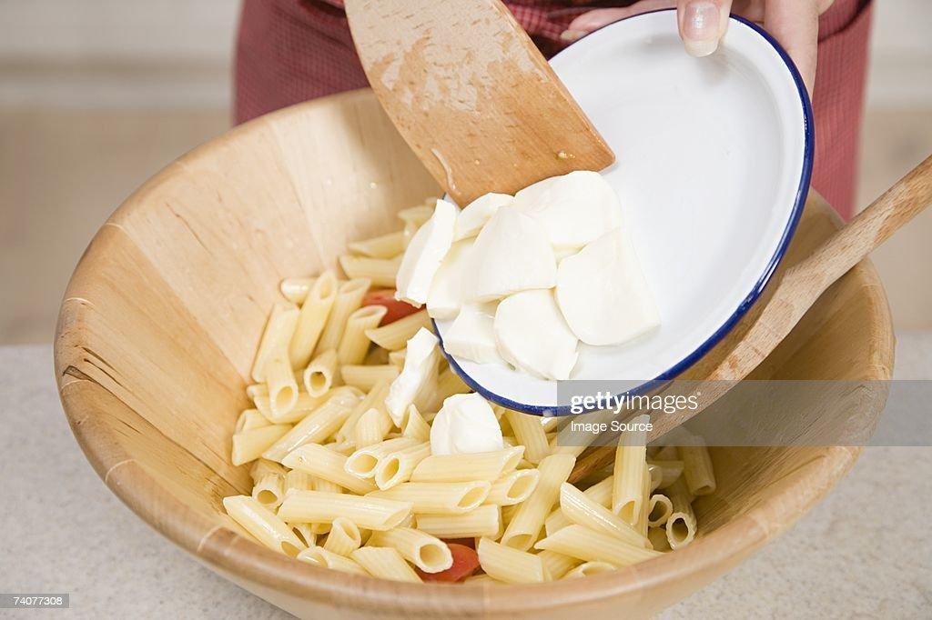 Person adding mozzarella to pasta : Stock Photo