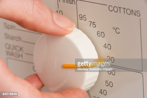 Person Adjusting Washing Machine Dial To Cold Wash : Stock Photo