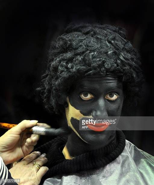 A person apply makeup on a man dressed as Black Peters prior to a celebration in a primary school on December 3 2010 in Soest Sinterklaas feast...