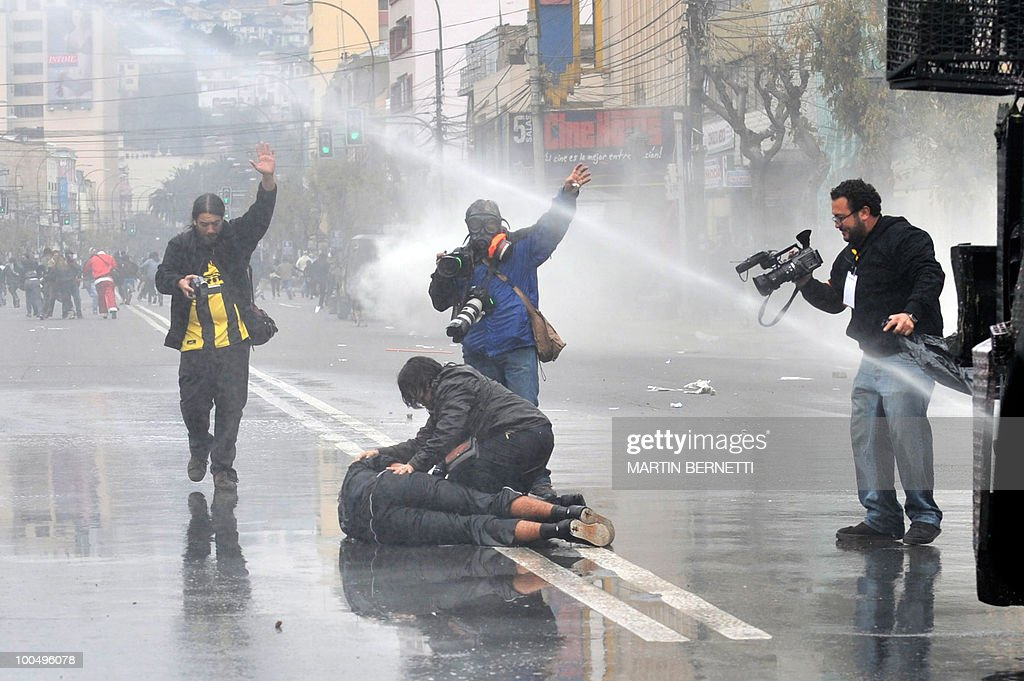 A person assists an injured demonstrator during clashes with the police at the surroundings of the Congress in Valparaiso, at the same time Chilean President Sebastian Pinera delivers his annual message to the nation on May 21, 2010.