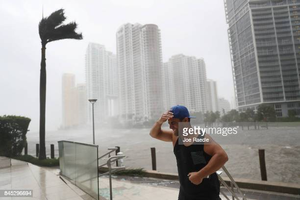 A person battles high winds and rain after taking pictures of the flooding along the Miami River as Hurricane Irma passes through on September 10...