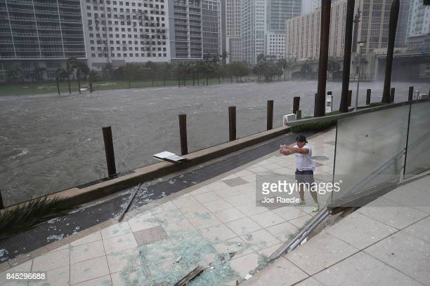 A person battles high winds and rain to take pictures of the flooding along the Miami River as Hurricane Irma passes through on September 10 2017 in...
