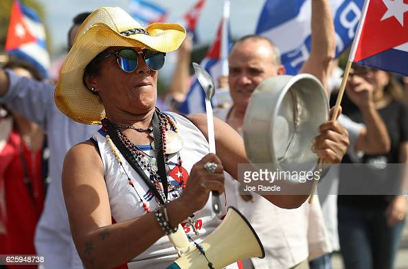 A person beats on a pot as she celebrates the news of the death of former Cuban President Fidel Castro outside the restaurant Versailles on November...