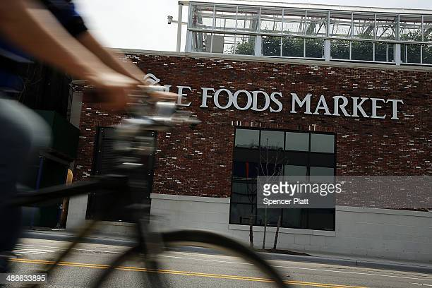 A person bikes past a Whole Foods Market in the Brooklyn borough on May 7 2014 in New York City Whole Foods Market an upscale grocery store that...