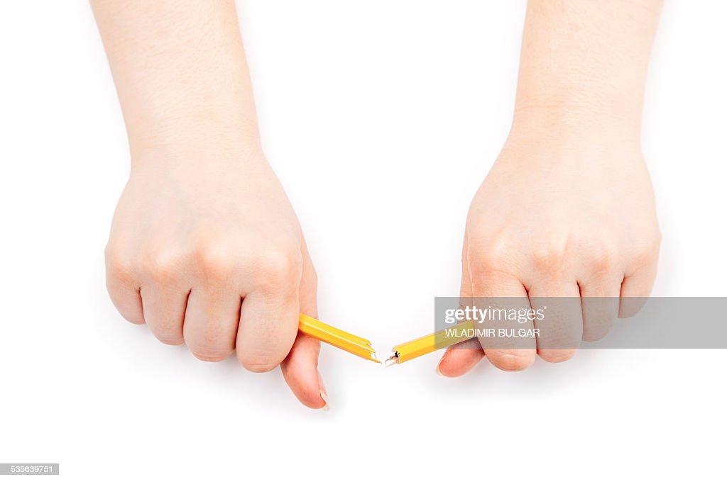 Person breaking a pencil