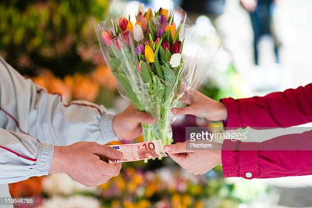 Person buying bunch of flowers from vendor