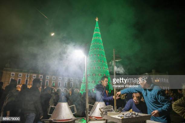 A person buys roasted chestnuts at a stall near the large Christmas tree and Christmas and New Year light displays in Praca do Comercio on December 9...
