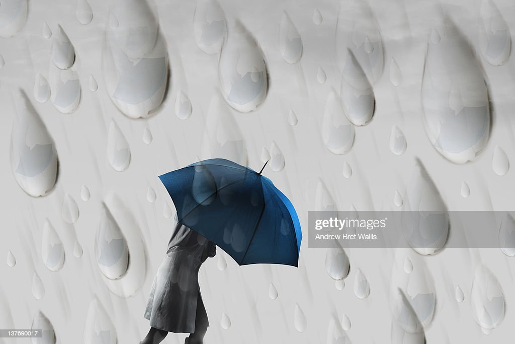 Person carrying an umbrella reflected in raindrops : Stock Photo