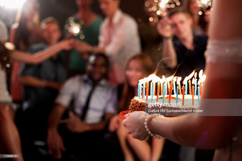 Person carrying birthday cake, group of friends in background : Stock Photo