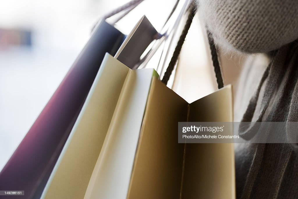 Person carrying shopping bags, cropped : Stock Photo
