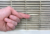 Person checks the contamination of the ventilation grill by swiping a finger along it