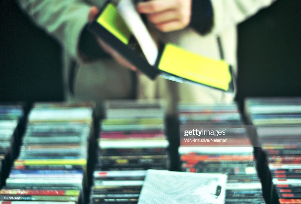 Person choosing CDs and DVDs in a music store, Shanghai, China