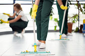 Close-up of person with yellow gloves cleaning the floor by using mop