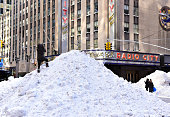 A person climbs a snow pile outside Radio City Music Hall after a blizzard on January 24 2016 in New York City