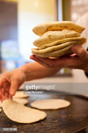 Person cooking hand made tortillas on grill : Stock Photo