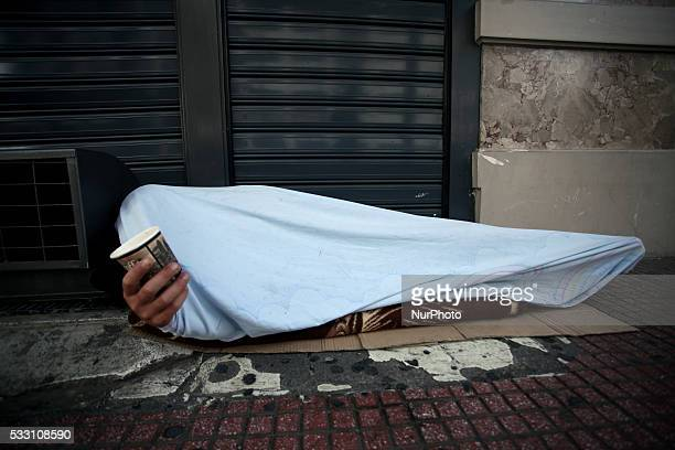 Person covered with a sheet holds a cup and asks for spare change in Athens city center May 12 2016