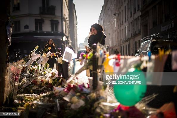 A person cries as she stands at a makeshift memorial for a tribute to the victims of a series of deadly attacks in Paris in front of the Casa Nostra...