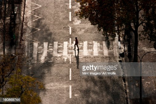 A person crosses a street paved with setts, Paris, France : Stock Photo