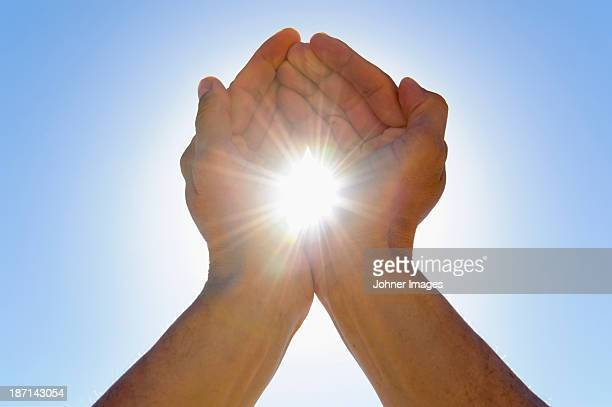 Person cupping hands against sky as to hold sun in between