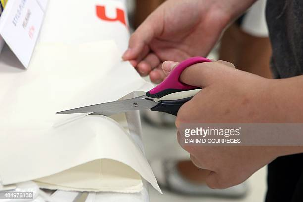 A person cuts paper with scissors for lefthanded users in the Salle du Pont du Buy in Brivela Gaillarde where writing and cooking workshops were...