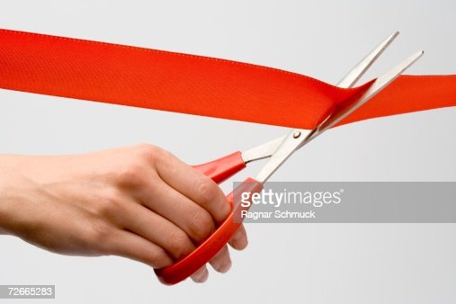 Person cutting red ribbon with scissors