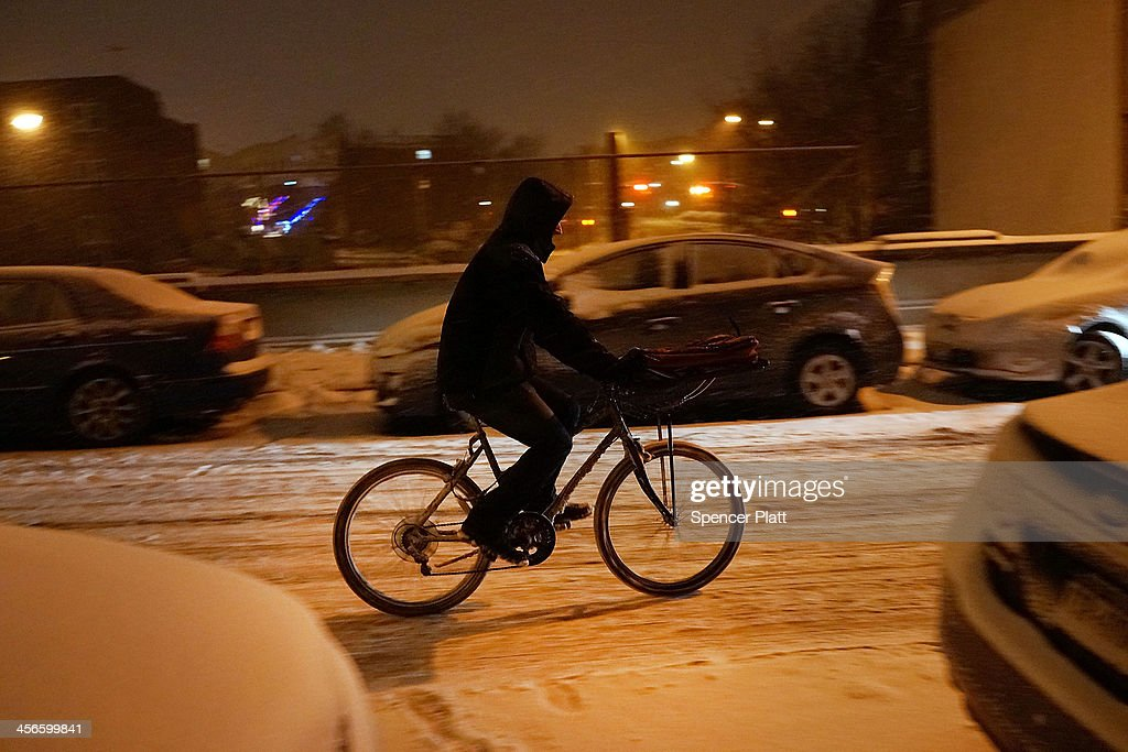 A person delivers food during a snow storm on December 14, 2013 in the Brooklyn borough of New York, United States. Much of the Northeast was hit Saturday by a storm stretching over 1,000 miles that could result in at least a foot of snow on parts of New England.