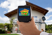 Close-up Of Person Detecting Heat Loss Outside House Using Infrared Thermal Camera