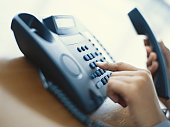 Person dialling telephone, close-up
