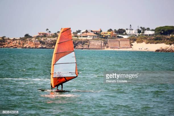 Person doing windsurfing in front of Puerto de Santa Maria